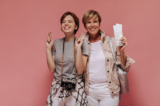 Gelukkige dames met kort kapsel en charmante glimlach in trendy outfit knuffelen, kruising vinger en kaartjes op roze achtergrond te houden.