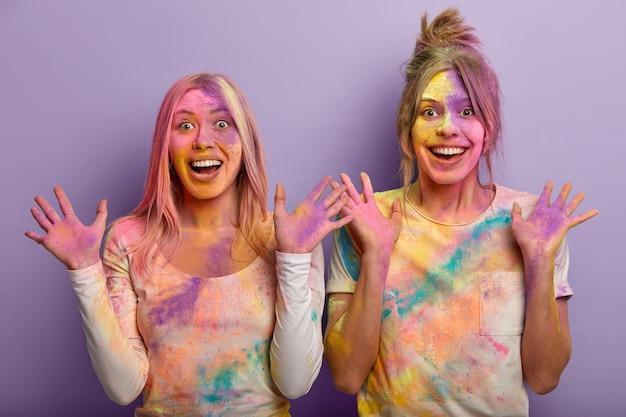 Gelukkige dames zien er hetzelfde uit, hebben de huid bedekt met kleurrijk poeder, tonen veelkleurige handpalmen, vieren holi-vakantie in maart, komen op een dynamisch kleurenfestival in india, spatten kleurstoffen op elkaar