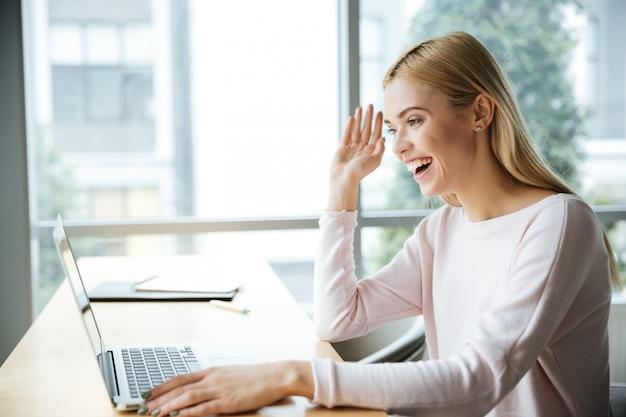 Gelukkige damezitting in bureaucorking terwijl het gebruiken van laptop