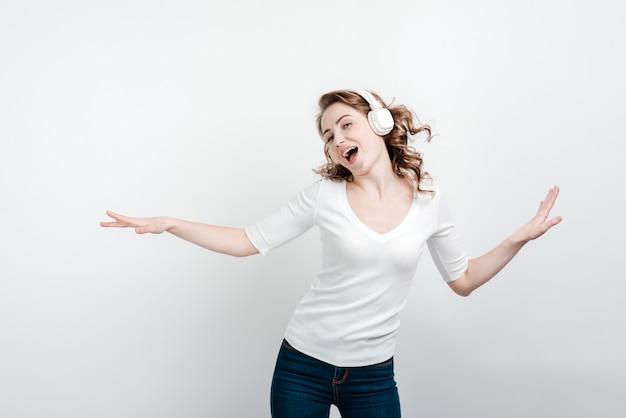 Gelukkige dansende vrouw in het draadloze oortelefoons zingen