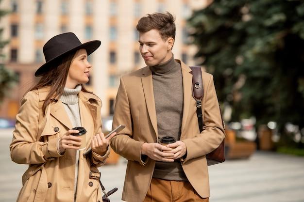 Gelukkige dates in beige vrijetijdskleding die praten terwijl ze onderweg koffie drinken in een stedelijke omgeving tegen het bouwen van een hedendaagse universiteit