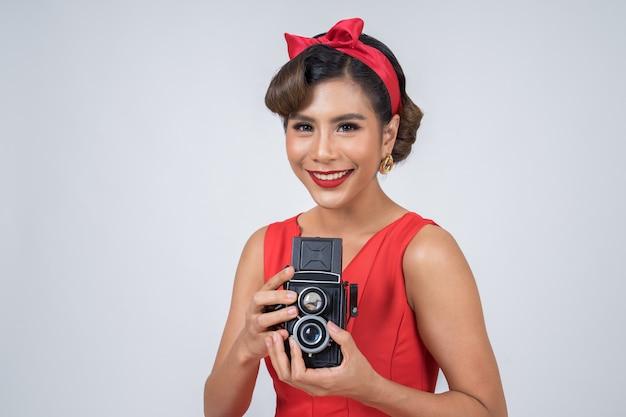 Gelukkige de fotograafhanden die van de maniervrouw retro uitstekende camera houden
