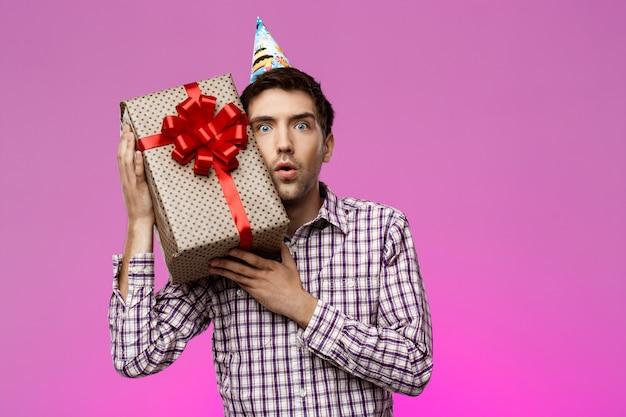 Gelukkige de verjaardagsgift van de jonge mensenholding in doos over purpere muur.