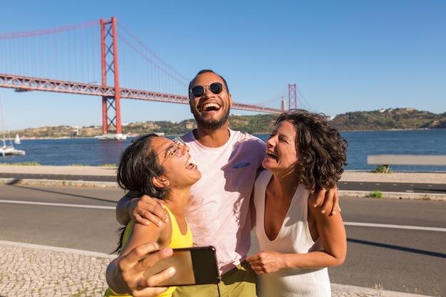 Gelukkige dichte vrienden die van vergadering genieten en groep selfie nemen