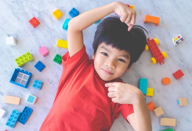 Gelukkige die jongen door kleurrijk stuk speelgoed blokken hoogste mening wordt omringd.