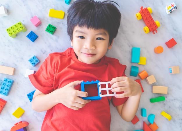 Gelukkige die jongen door kleurrijke stuk speelgoed blokken hoogste mening wordt omringd.