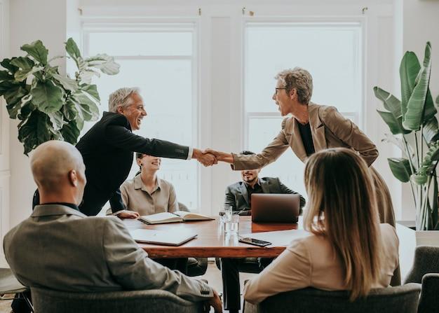 Gelukkige diverse zakenmensen die een deal sluiten