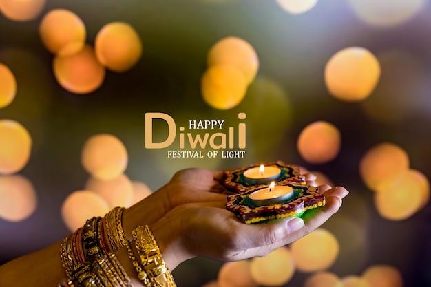 Gelukkige diwali - vrouwenhanden met henna die aangestoken kaars houden die op donkere achtergrond wordt geïsoleerd. clay diya-lampen aangestoken tijdens dipavali, hindoe-festival van lichtviering. ruimte voor tekst kopiëren.