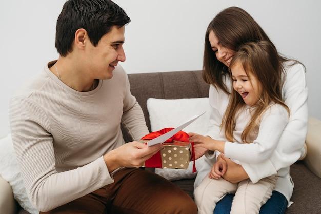 Gelukkige dochter die geschenk van ouders thuis ontvangt