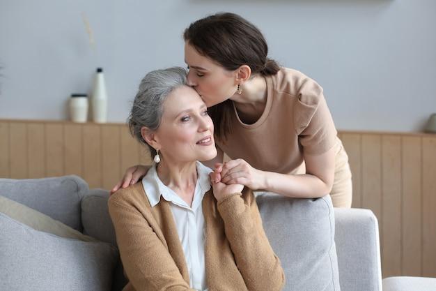 Gelukkige dochter die oudere moeder knuffelt, achter de bank in de woonkamer staat en thuis geniet van een teder moment