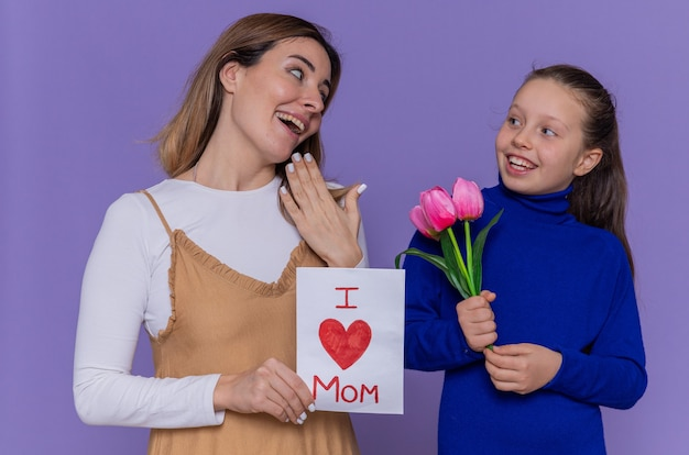 Gelukkige dochter die wenskaart en tulpenbloemen geeft voor haar verraste en glimlachende moeder die internationale vrouwendag viert die zich over purpere muur bevindt