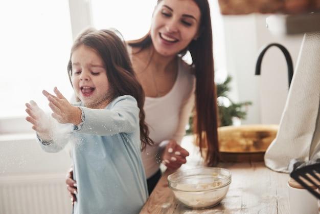 Gelukkige dochter en moeder bereiden samen bakkerijproducten. kleine helper in de keuken.