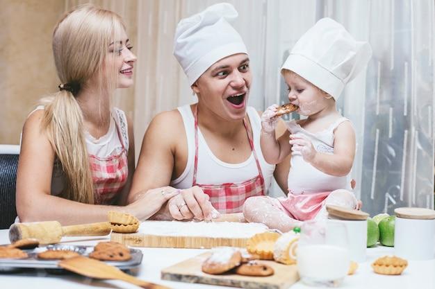 Gelukkige dochter met vader en moeder in huiskeuken lachen en samen eten bereiden, met liefde