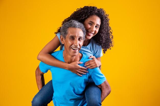 Gelukkige dochter op vaders rug op gele achtergrond.