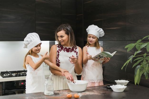 Gelukkige dochters die chef-kokhoed met moeder dragen die voedsel in keuken voorbereiden