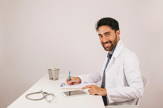 Gelukkige dokter met tablet in het kantoor