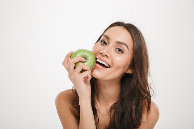 Gelukkige donkerbruine vrouw die appel eet en de camera over grijs bekijkt