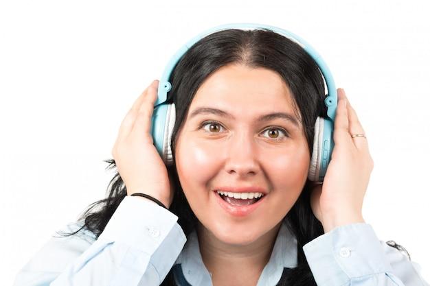 Gelukkige donkerbruine vrouw die met die hoofdtelefoons aan muziek luisteren op wit wordt geïsoleerd.