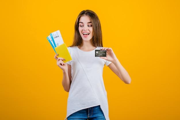 Gelukkige donkerbruine vrouw met vliegtickets in paspoort en creditcard die over geel wordt geïsoleerd