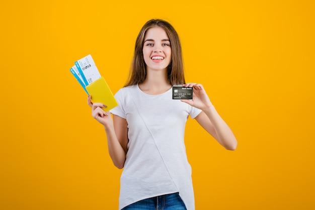 Gelukkige donkerbruine vrouw met vliegtuigkaartjes in paspoort en creditcard die over geel wordt geïsoleerd