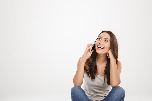 Gelukkige donkerbruine vrouwenzitting op de vloer en het spreken door smartphone terwijl het kijken weg over grijs