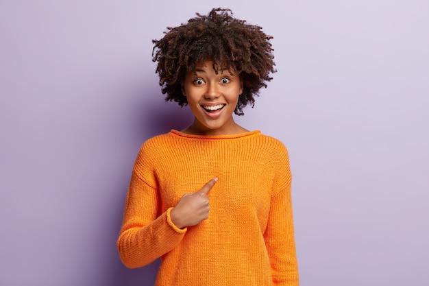 Gelukkige donkere jongedame wijst naar zichzelf, verheugt zich dat ze wordt gekozen, draagt een oranje casual trui, glimlacht, geïsoleerd over paarse muur. glimlachende optimistische vrouw zegt dat je mij bedoelt.