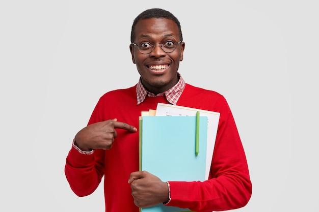 Gelukkige donkere man wijst naar zichzelf, heeft een blije uitdrukking, brede glimlach, draagt een leerboek, vraagt of hij echt een uitstekend cijfer verdient