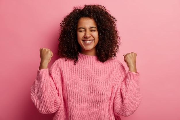 Gelukkige donkere tiener steekt gebalde vuisten op, viert overwinning en succes, verwierf wenselijke wens, glimlacht breed, gekleed in gebreide trui, geïsoleerd op roze muur.