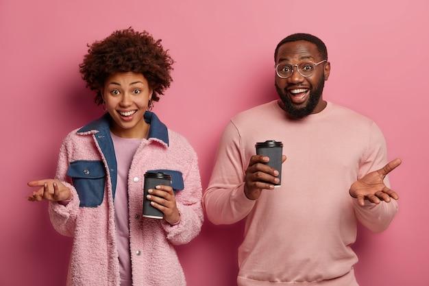 Gelukkige donkere vriendin en vriend drinken cafeïnedrank, houden papieren bekers vast, gekleed in roze kleding, genieten van vrije tijd, zijn dol op favoriete drank