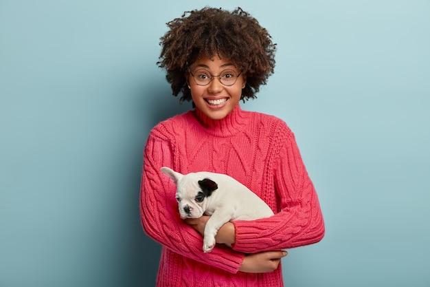 Gelukkige donkere vrouw in roze gebreide trui