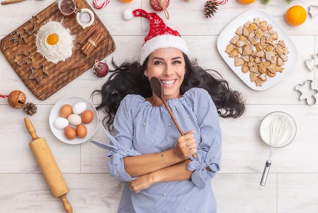 Gelukkige donkerharige vrouw in kerstmuts die een houten lepel vasthoudt en op de grond ligt met traditionele ingrediënten zoals meel, eieren, sinaasappels en ook bakvormen, roller of peperkoek.