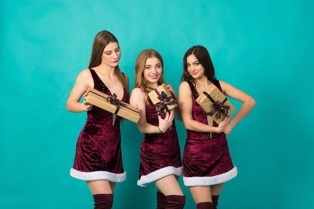 Gelukkige drie mooie meisjes met verschillende haarkleur, sneeuwmeisje in kerstkostuums met cadeauzakje.