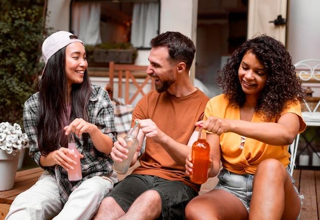 Gelukkige drie vrienden die hun vooraanzicht van de dranken openen
