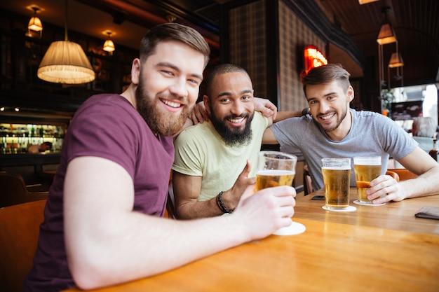 Gelukkige drie vrienden zitten in biercafé en kijken naar de voorkant