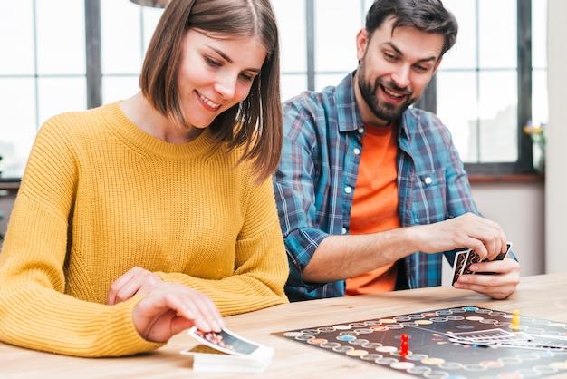Gelukkige echtgenoot en vrouw die het adreskaartjespel spelen