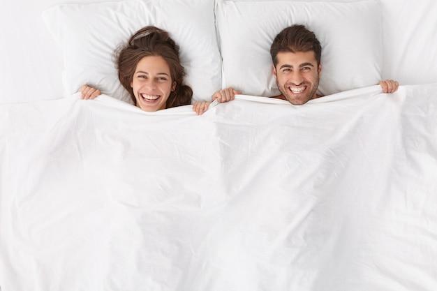 Gelukkige echtgenoten brengen graag tijd samen door, liggen onder een witte deken, hebben positieve uitdrukkingen en glimlachen, blijven in bed, worden wakker na het slapen of slapen vroeg in de ochtend, voelen zich vernieuwd na een diepe, gezonde nacht,