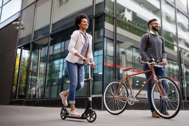 Gelukkige eco-zakenmensen gaan werken met fiets, elektrische scooter op stedelijke straat