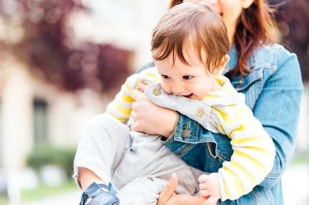Gelukkige eenjarige baby gegrepen door zijn moeder