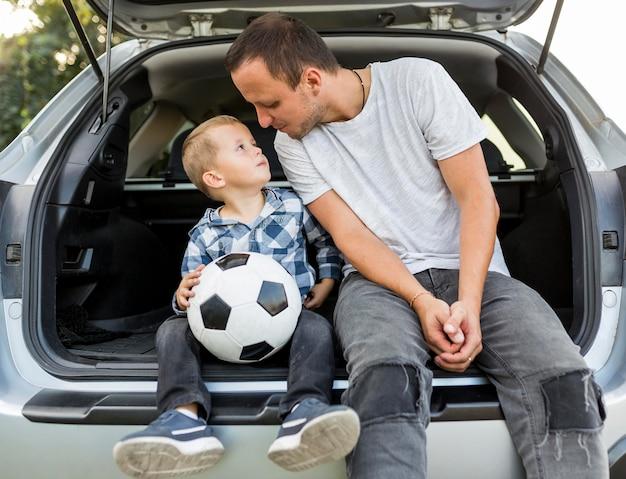 Gelukkige eenouderlijke familie achter in de auto