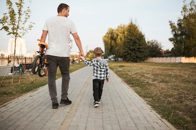 Gelukkige eenouderlijke familie wandelen in het park