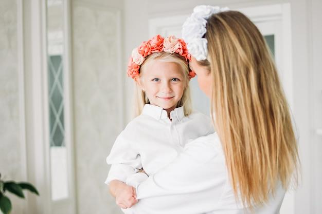 Gelukkige eerlijke lange haarmamma en leuke dochter in kronen van bloemen bij woonkamer, gelukkige familielevensstijl