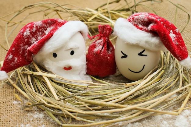 Gelukkige eieren met geschilderde gezichten in het nest voor kerstmis