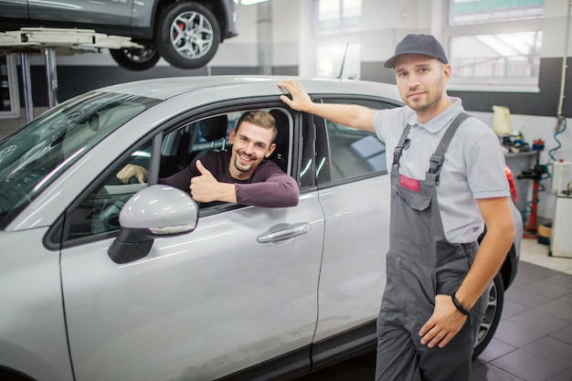 Gelukkige eigenaar zit in de auto en glimlacht. hij houdt zijn grote duim omhoog. werknemer staan op auto en houdt zijn hand op het dak van de auto. ze poseren op camera.