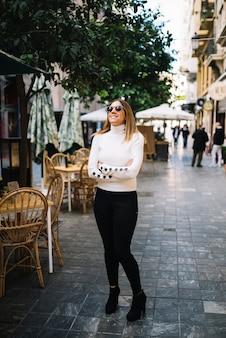 Gelukkige elegante jonge vrouw met zonnebril dichtbij straatkoffie in stad