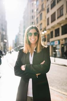 Gelukkige elegante jonge vrouw met zonnebril op straat in zonnige dag