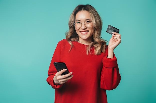 Gelukkige emotionele jonge vrouw poseren geïsoleerd over blauwe muur muur met behulp van mobiele telefoon met creditcard