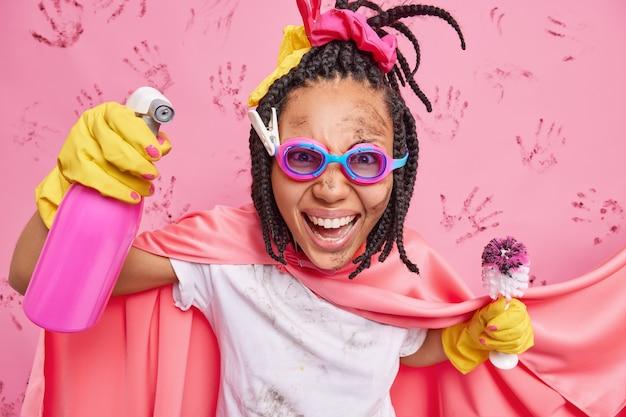 Gelukkige emotionele vrouw die superheld schoonmaakt, houdt chemisch spuitmiddel vast en vuile borstel helpt je met huishoudelijk werk draagt een veiligheidsbril die over roze muur wordt geïsoleerd
