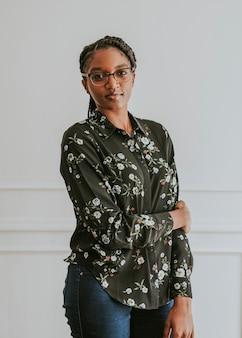 Gelukkige empowerment van zwarte vrouw die bij een witte muur staat