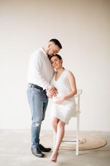 Gelukkige en aantrekkelijke zwangere vrouw en haar echtgenoot die in studio stellen