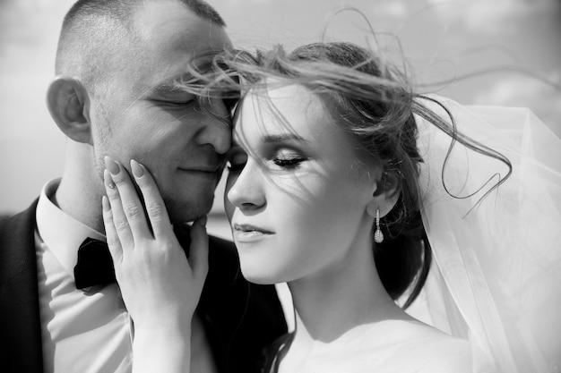 Gelukkige en bruid en bruidegom die, liefde koesteren kussen
